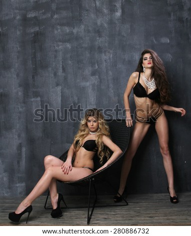 Two beautiful women in erotic lingerie, photo in front of blue studio background - stock photo