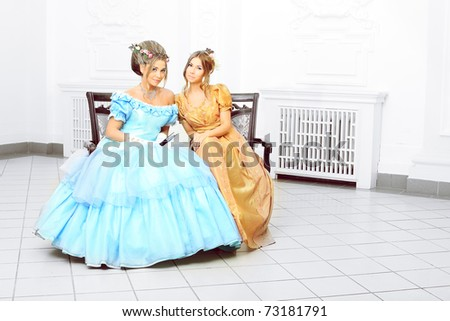 Two beautiful women in medieval era dresses. - stock photo