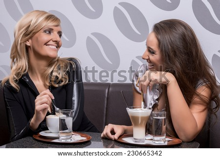Two beautiful women laughing over a coffee at the coffee shop. - stock photo