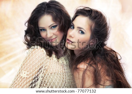 Two beautiful women on shining background