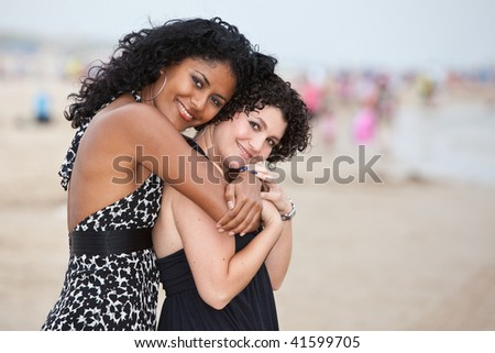 Two beautiful women on the beach in an embrace - stock photo