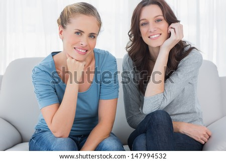 Two beautiful women posing while sitting on the couch and looking at camera - stock photo