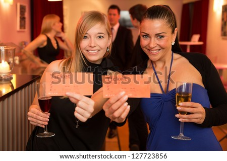 Two beautiful women presenting tickets for a theatre, cinema or a concert - stock photo