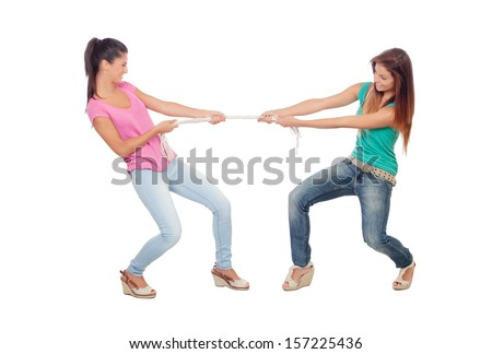 Two beautiful women pulling a rope isolated on a white background - stock photo