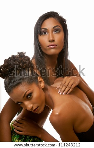 Two beautiful women share an intimate but glamorous moment - stock photo