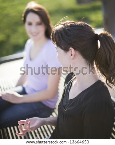two beautiful women sitting on bench having a conversation