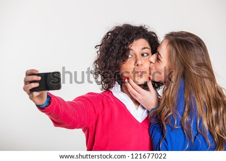 Two Beautiful Women Taking Self Portrait with Mobile Phone - stock photo