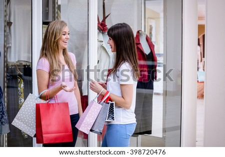 Two beautiful women talking outside a shop in shopping mall
