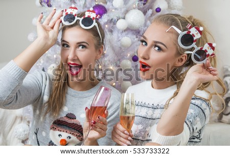 two beautiful women wearing christmas jumpers and sunglasses having champagne against christmas tree on new years eve