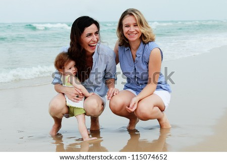 two beautiful women with a baby on the beach - stock photo