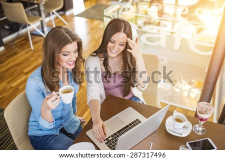 Two beautiful women with laptop in cafe - stock photo