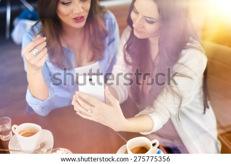 Two beautiful women with smart phone in cafe - stock photo