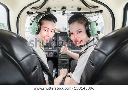 two beautiful young Asian pilot student looking at the back seat holding up thumb, wearing their uniform and headsets. In small light aircraft ready to take off - stock photo