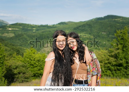 Two beautiful young boho sisters hugging and smiling outdoors. Fashionable bohemian with long back hair wearing hippie summer outfit. Horizontal, no retouch, natural light. - stock photo