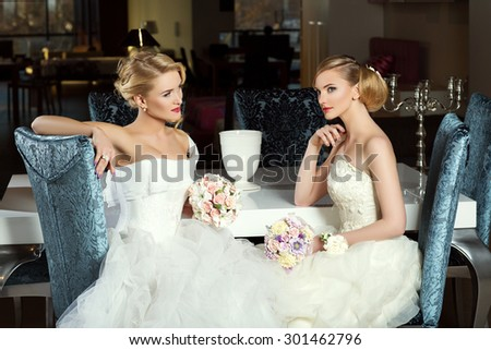 Two beautiful young brides in fashion wedding gowns sitting near table. Interior shot. - stock photo