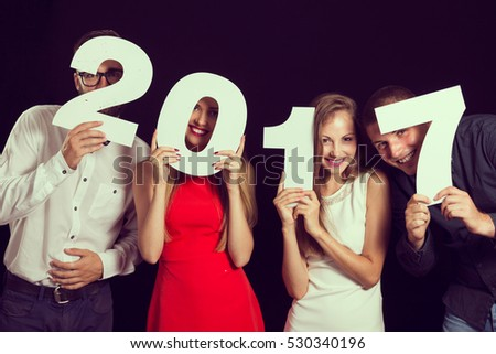 Two beautiful young couples having fun at New Year's Eve Party, holding cardboard numbers 2017