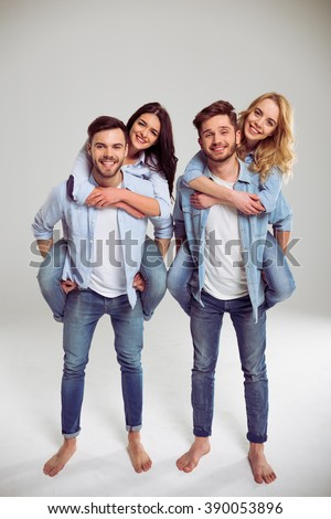 Two beautiful young couples in jeans are looking at camera and smiling, standing barefoot on a gray background. Girls pickaback - stock photo