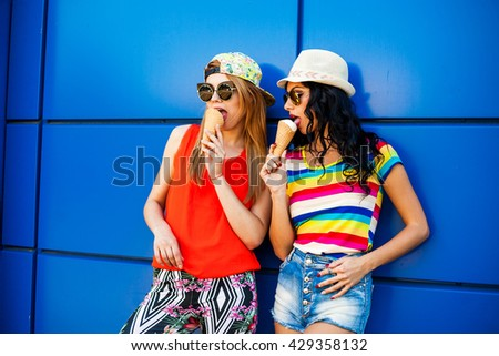 Two beautiful young cute bold sexy girl eating ice cream, colorful casual wear, denim shorts, leggings, bright T-shirts, sunglasses, hat, cap, urban style, blue background, blonde and brunette - stock photo