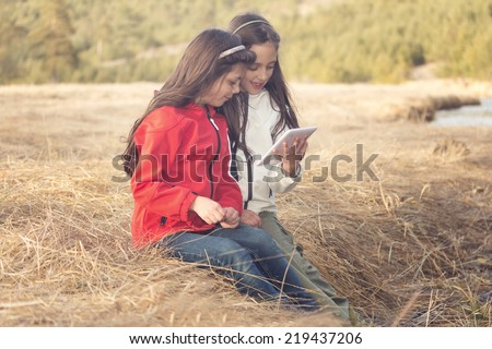 Two beautiful young girl using digital tablet in nature - stock photo