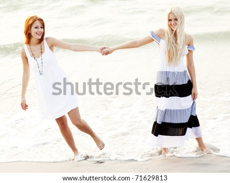Two beautiful young girlfriends on the beach at sunset. Photo with counter-light on background. - stock photo