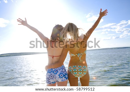 two beautiful young girlfriends opened her hands with delight at the blue sea and sky - stock photo