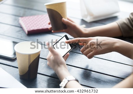 Two beautiful young girlfriends using app on smartphone in modern coffee shop interior. Close-up of hands and empty phone display. Woman touching mobile phone screen with blank white copy space - stock photo