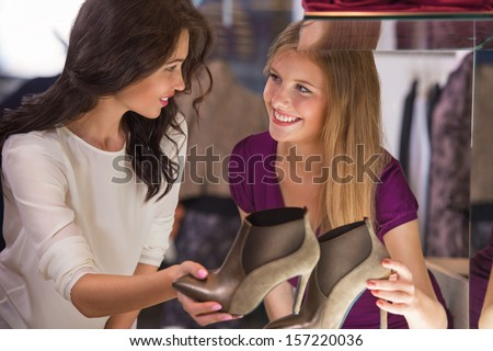 Two beautiful young girls choosing shoes at store. Holding pair near showcase and speaking - stock photo