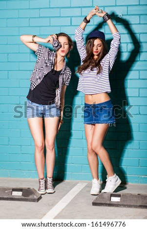 two beautiful young girls dance, take pictures and have fun at parking lot - stock photo
