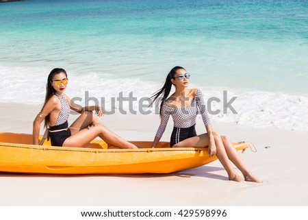 Two Beautiful Young Girls have Happy Life enjoying Sunshine, sunbath and Ocean Beach during Vacation Holiday, both sitting on yellow orange Kayak canoe.  Playful and Relax Concept - stock photo