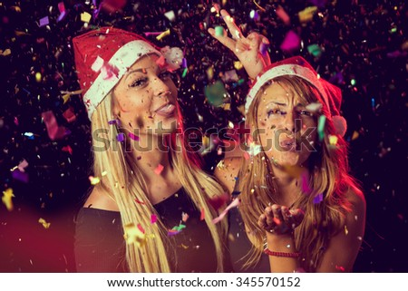 Two beautiful young girls having fun at New Year's Eve party, sending kisses - stock photo