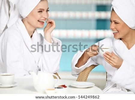 Two beautiful young girls having fun at spa salon - stock photo
