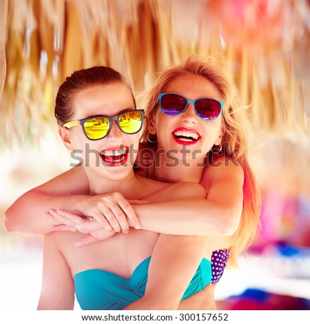 two beautiful young girls having fun on beach during summer vacation - stock photo