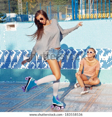 two beautiful young girls in an empty pool, one watches the other skating on the rollers  - stock photo