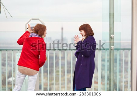 Two beautiful young girls in Paris looking at the Eiffel tower from the Montparnasse tower - stock photo