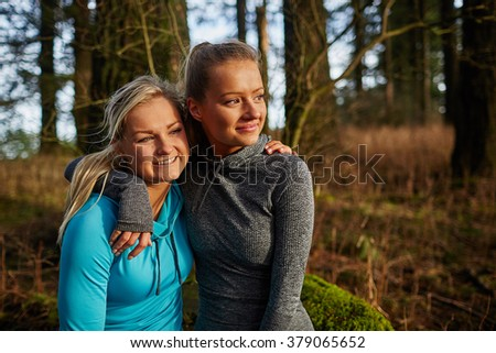 two beautiful young girls sitting on log arms around watching sunset