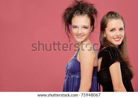 Two beautiful young girls smile and stand backs to each other, on red background - stock photo