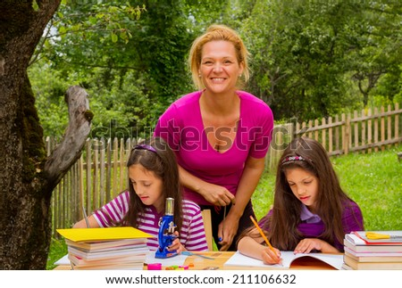 Two beautiful young happy students learn outdoors with teacher.Two beautiful young happy students learn outdoors with mother. - stock photo