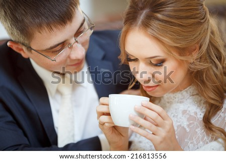Two beautiful young people, bride and groom sitting at a table in a cafe.With a good mood, they are celebrating their wedding day, drinking coffee from a white cup.
