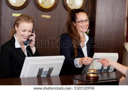 Two beautiful young stylish receptionists at a reception desk, one talking on the telephone and the other handing a card to a customer - stock photo