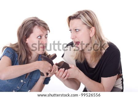 two beautiful young woman compete for a shoe - stock photo