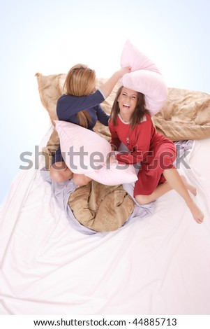 Two beautiful young woman fighting with pillows in bed