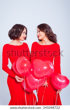 Two beautiful young woman in a long red dress with balloons in the form of heart in his hands. Valentine's Day. Twins.