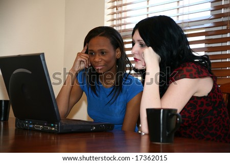 Two beautiful young woman working on laptop together at home. - stock photo