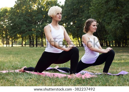 Two beautiful young womans doing stretching exercise on green grass at park. Yoga - stock photo