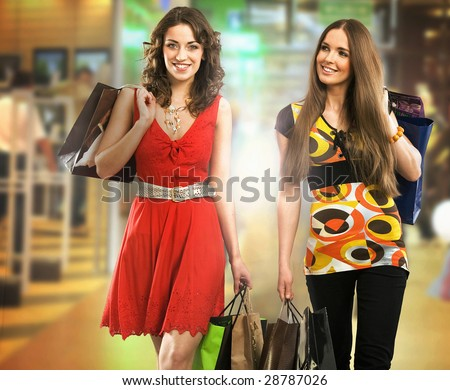 Two beautiful young women at a shopping mall with bags - stock photo