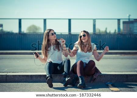 two beautiful young women dancing in the city - stock photo
