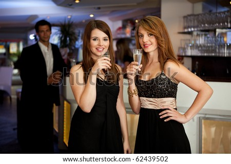 Two beautiful young women drinking chanpagne
