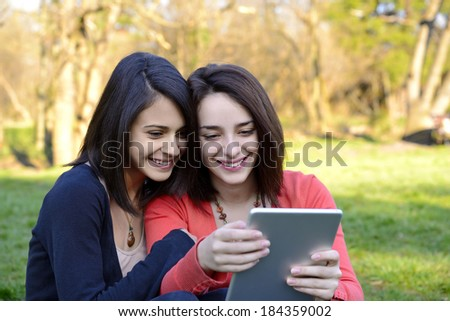 Two beautiful young women having fun while browsing a tablet outside  - stock photo
