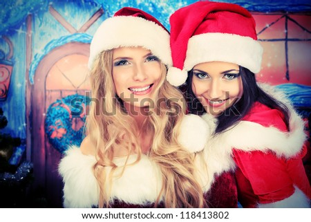 Two beautiful young women in Christmas clothes posing over Christmas background.