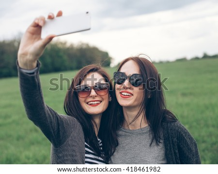 Two beautiful young women outdoors taking pictures of themselves on a mobile phone
